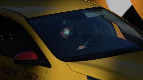 Водитель в защитной маске за рулем такси в Москве