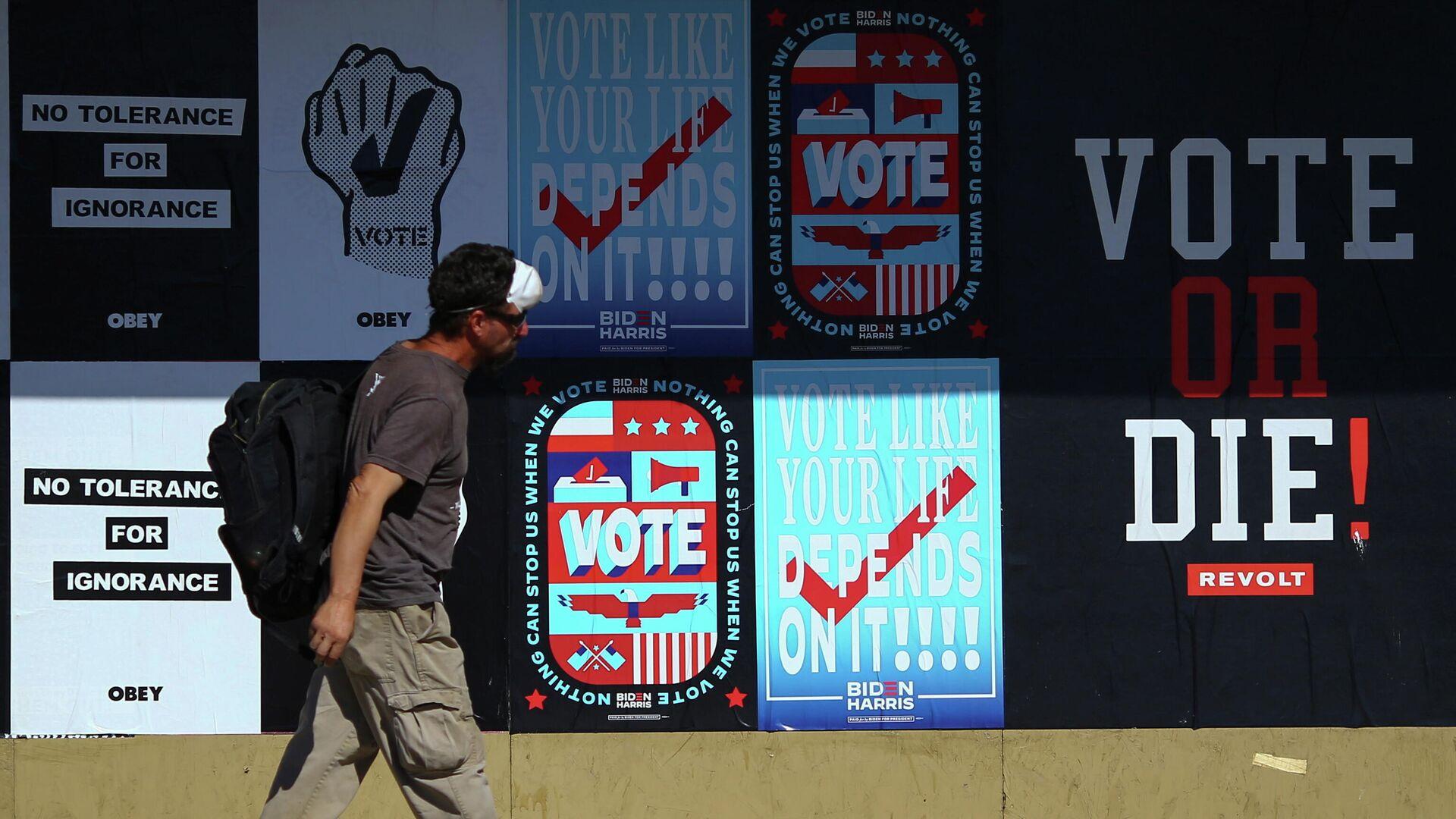 Мужчина проходит мимо предвыборных плакатов в городе Фениксе штата Аризона в США - РИА Новости, 1920, 04.11.2020