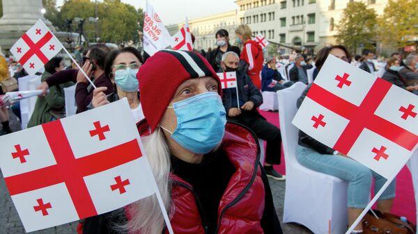 Участники демонстрации в поддержку партии Единое национальное движение в Тбилиси