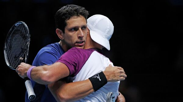 Poland's Lukas Kubot (R) and Brazil's Marcelo Melo (L) embrace as they celebrate their win over Croatia's Ivan Dodig and Slovakia's Filip Polasek in their men's doubles round-robin match on day one of the ATP World Tour Finals tennis tournament at the O2 Arena in London on November 10, 2019. (Photo by Adrian DENNIS / AFP)