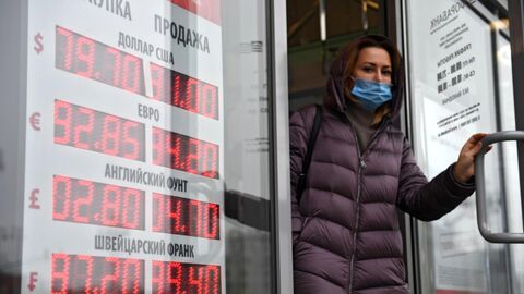 Девушка выходит из обменного пункта валют в Москве