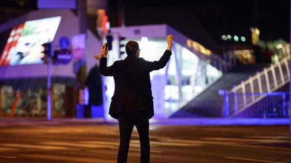 Мужчина держит руки вверх, пока полицейские проверяют его на улице после перестрелки в Вене, Австрия