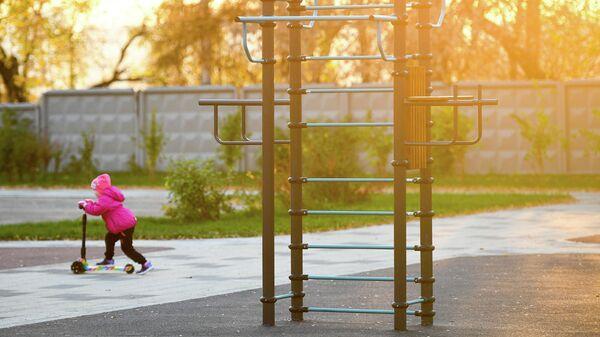 Ребенок катается на самокате у спортивной площадки в Капотне