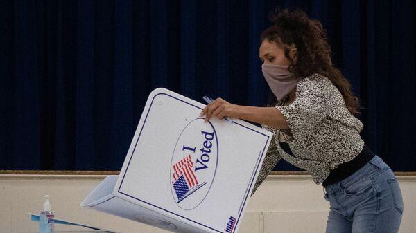 Сотрудница избирательной комиссии после окончания голосования на президентских выборах в США