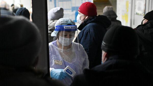 Измерение температуры людям при входе в поликлинике городской больницы №2 в Омске