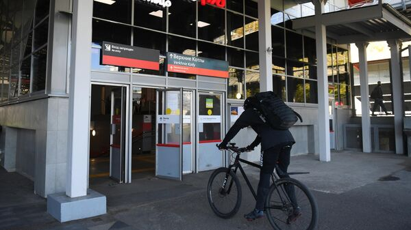 Человек на велосипеде возле станции МЦК Верхние Котлы в Москве.