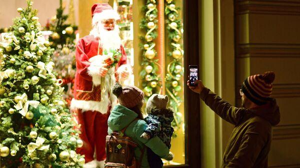 Прохожие фотографируют Санта Клауса в витрине на Никольской улице в Москве