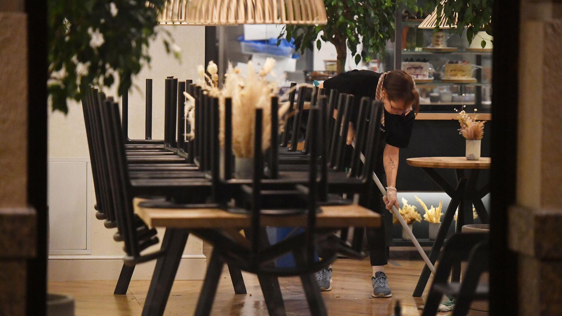 Уборщица моет пол в закрытом ресторане на одной из улиц в Москве - РИА Новости, 1920, 16.11.2020