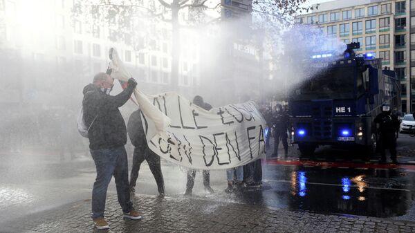 Полицейские используют водометы против участников акции протеста во Франкфурте, Германия