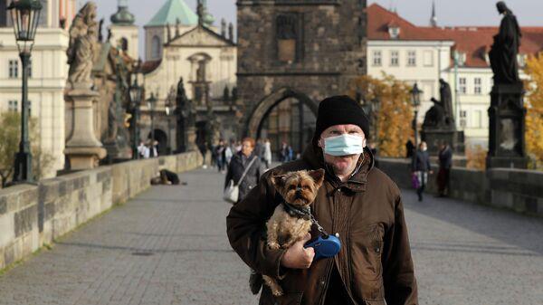 Мужчина в маске с собакой на Карловом мосту в Праге