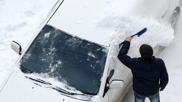 Мужчина сметает снег с машины