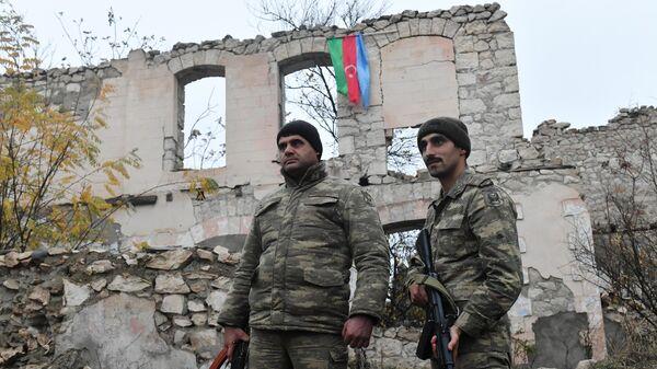 Военнослужащие у разрушенного здания в Физулинском районе Азербайджана