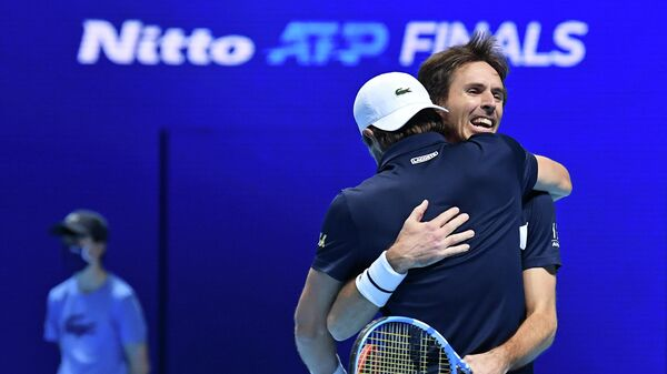 France's Edouard Roger-Vasselin (R) and Austria's Jurgen Melzer (front) embrace after winnning the match against Australia's John Peers and New Zealand's Michael Venus in their men's doubles round-robin match on day four of the ATP World Tour Finals tennis tournament at the O2 Arena in London on November 18, 2020. (Photo by Glyn KIRK / AFP)