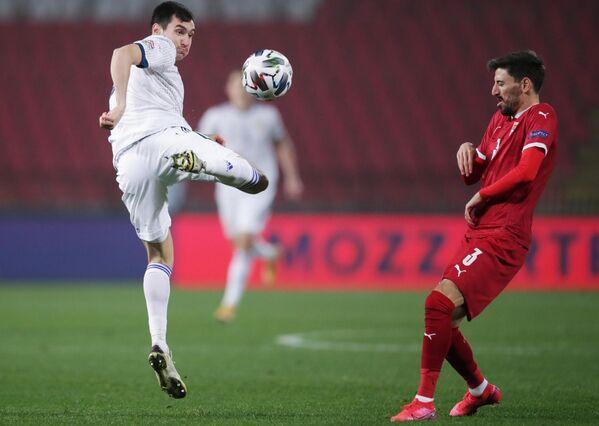 Защитник сборной России Вячеслав Караваев (слева) и полузащитник сборной Сербии Филип Младенович