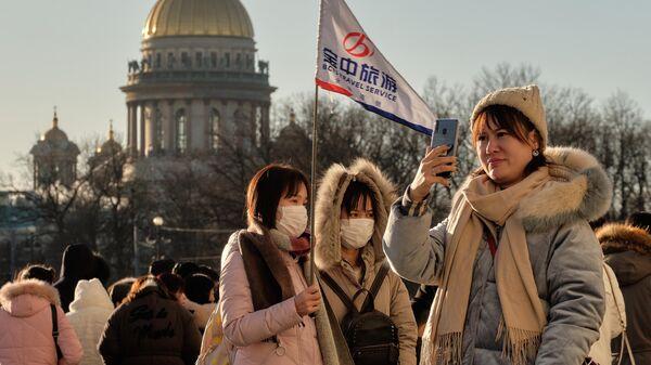 Китайские туристы на Дворцовой площади в Санкт-Петербурге