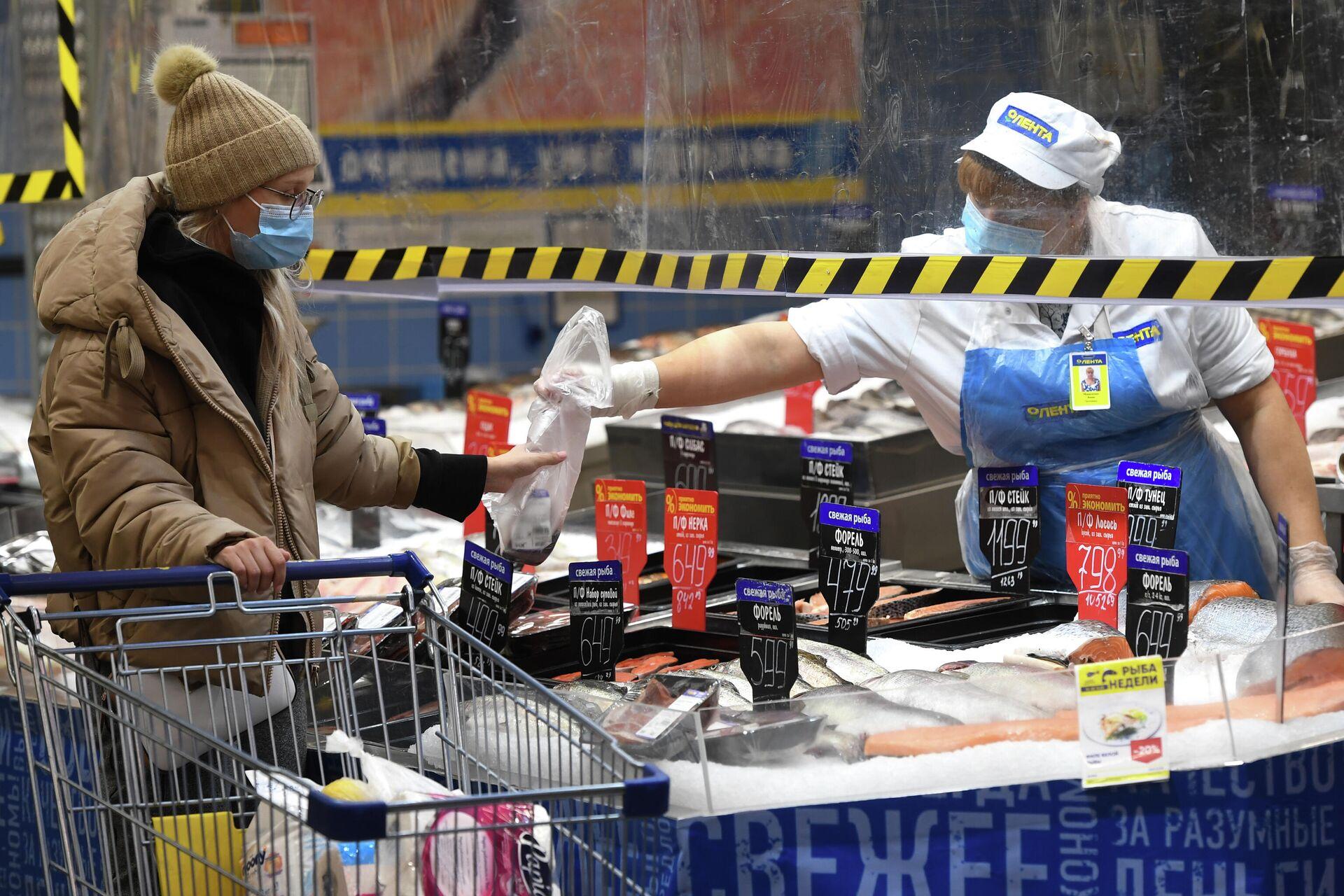 Покупатель и продавец в рыбном отделе гипермаркета Лента в период пандемии коронавируса в Новосибирске - РИА Новости, 1920, 20.11.2020