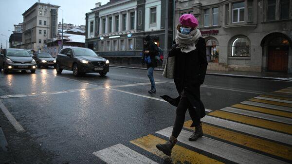 Девушка в защитной маске на улице в Москве