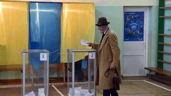 Мужчина голосует на избирательном участке во Львове