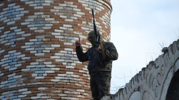 Вооруженный мужчина на крыше мечети Джума в Агдаме