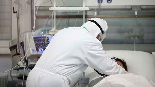 Медицинский работник около пациента в реанимационном отделении в ГБУЗ Волгоградская областная инфекционная больница No2 в Волгоградской области
