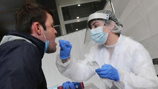 Медицинский работник мобильного пункта сдачи анализа на COVID-19 берет мазок у пассажира в международном аэропорту Внуково