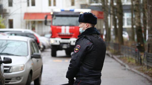 Сотрудник полиции у жилого дома в городе Колпино Ленинградской области, где мужчина держит в заложниках детей в квартире