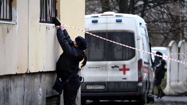 Сотрудница полиции натягивает оградительную ленту у жилого дома в городе Колпино Ленинградской области, где мужчина держит в заложниках детей в квартире