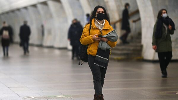 Девушка в защитной маске на одной из станций Московского метрополитена