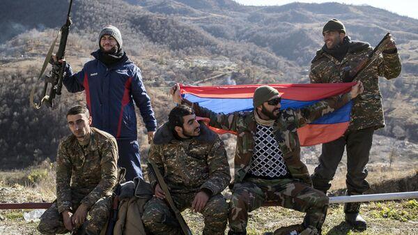 Вооруженные мужчины с флагом Армении в Кельбаджарском районе Нагорного Карабаха накануне передачи Азербайджану