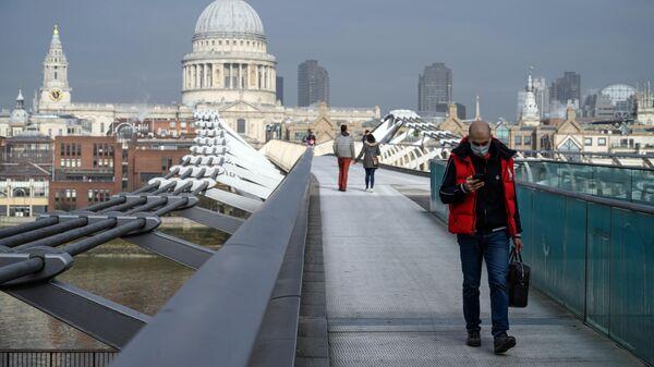 Прохожие на мосту Тысячелетия в Лондоне во время карантина, введенного в связи с коронавирусом