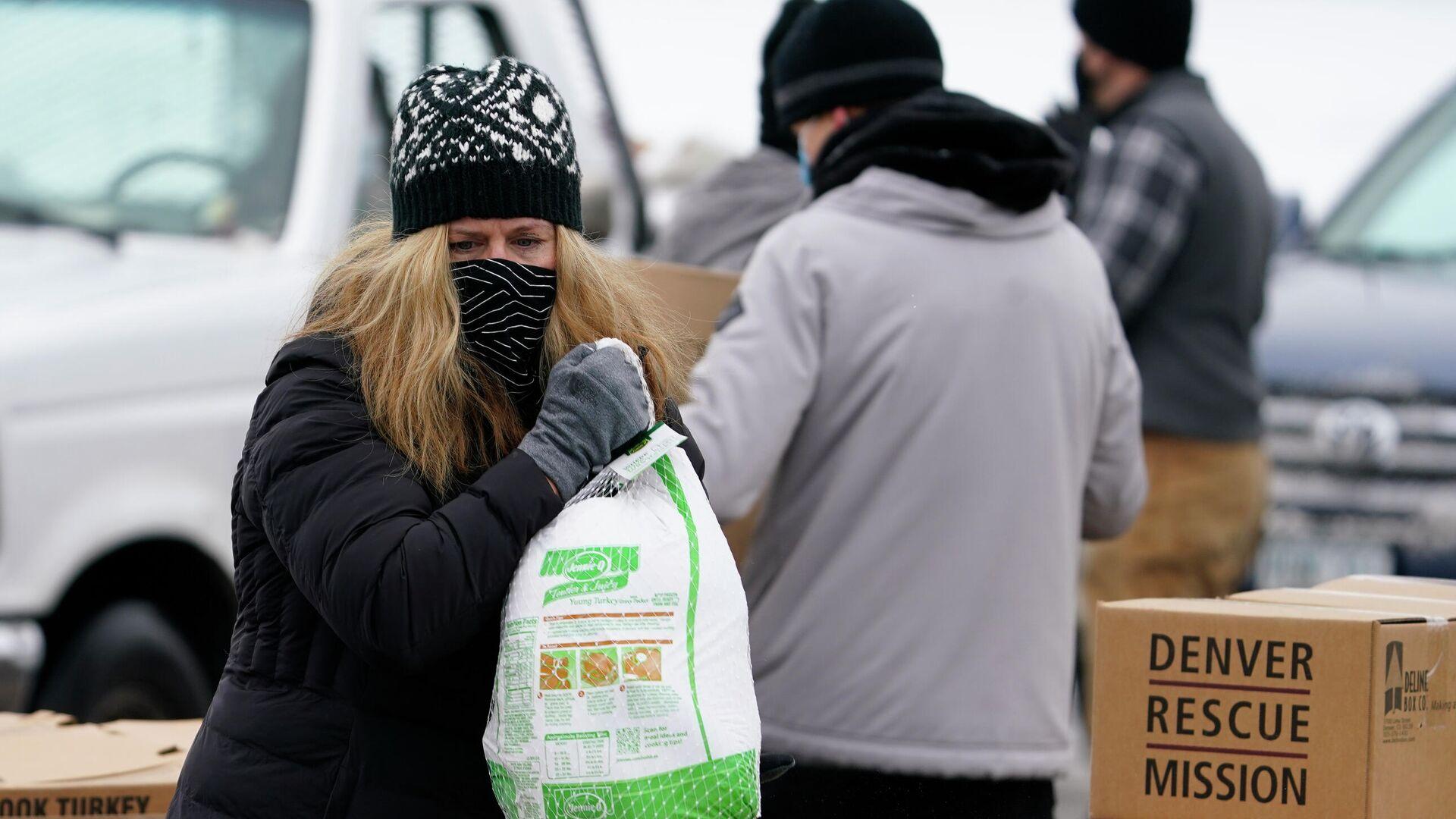 Волонтер с замороженной индейкой во время раздачи еды в рамках акции Банкет в коробке - РИА Новости, 1920, 28.11.2020
