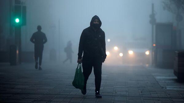 Пешеход в защитной маске на улице в районе Уолтамстоу в Лондоне