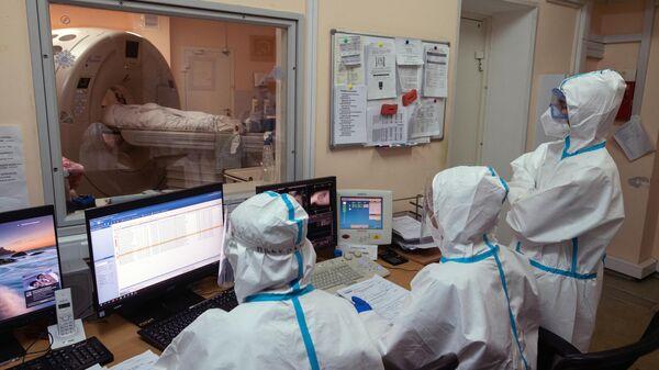 Медицинские работники и пациент в кабинете компьютерной томографии госпиталя COVID-19 в городской клинической больнице № 52 в Москве.