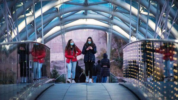Девушки в защитных масках на одной из улиц в Тбилиси