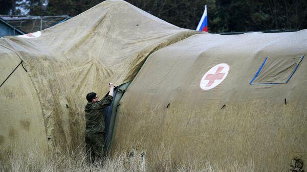 Российская военнослужащая закрепляет тент на каркасном модуле на территории мобильного полевого госпиталя неподалеку от Степанакерта