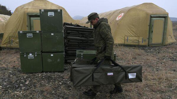 Российский военнослужащий выгружает оборудование на территории мобильного полевого госпиталя неподалеку от Степанакерта