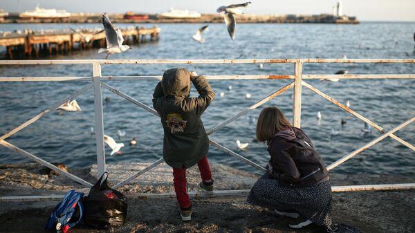 Женщина с ребенком гуляют по набережной Ялты