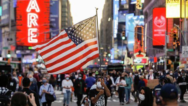 Мужчина с флагом США на Таймс-сквер в Нью-Йорке