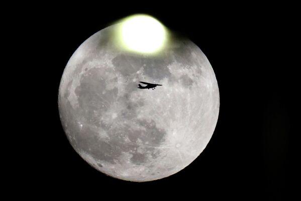 Частный самолет пролетает мимо бобровой луны около аэропорта имени Бен-Гуриона в Тель-Авиве, Израиль
