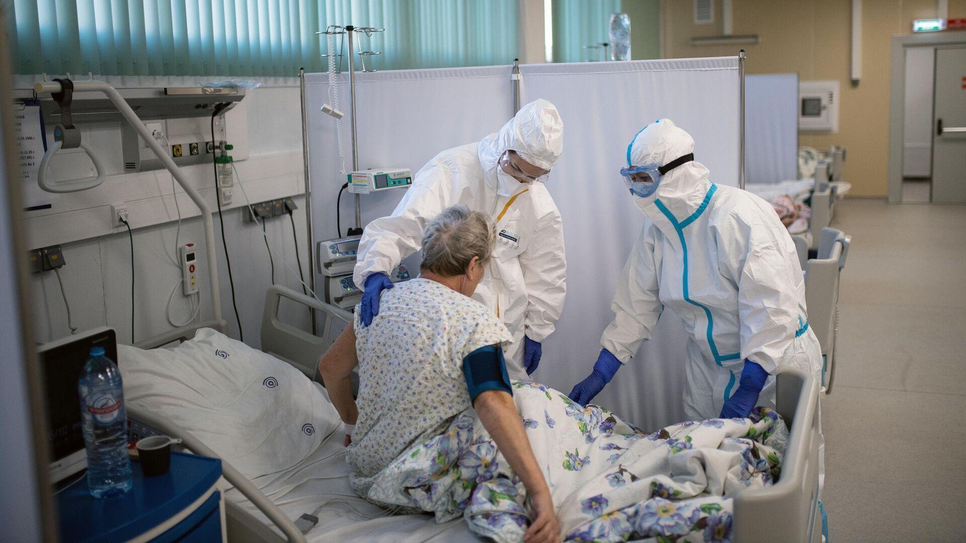 Медицинские работники и пациент в отделении реанимации и интенсивной терапии в госпитале для больных COVID-19  - РИА Новости, 1920, 04.12.2020
