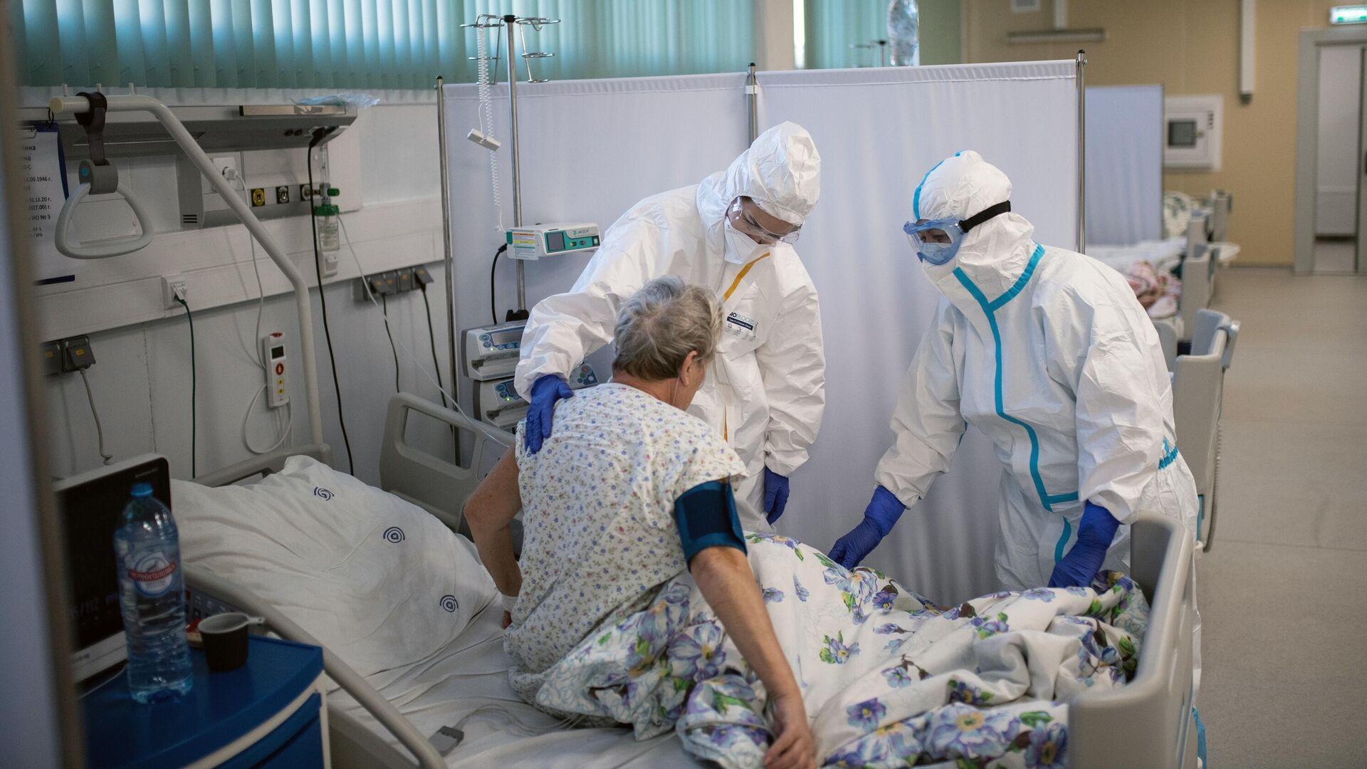 Медицинские работники и пациент в отделении реанимации и интенсивной терапии в госпитале для больных COVID-19  - РИА Новости, 1920, 08.12.2020