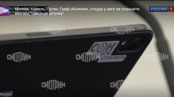Наклейка на планшете председателя правления Сбербанка России Германа Грефа во время эфира на телеканале Россия 1