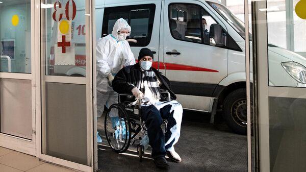 Сотрудник скорой медицинской помощи доставляет пациента в приемное отделение
