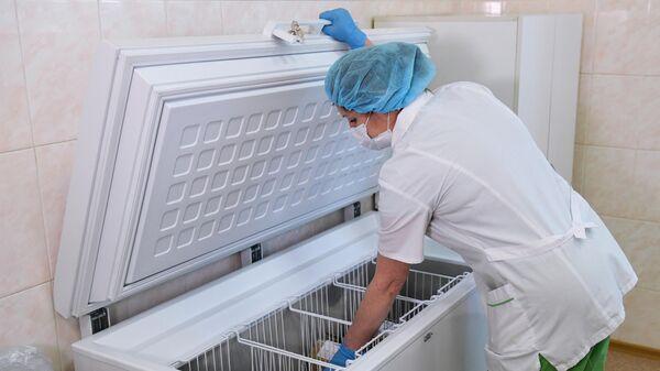 Медицинская сестра достает упаковку с вакциной от коронавируса Гам-Ковид-Вак из холодильника