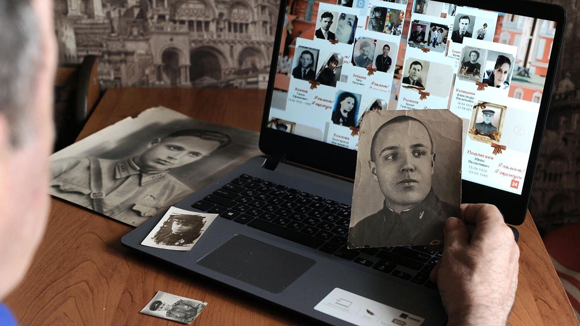 Мужчина смотрит онлайн-трансляцию акции Бессмертный полк - РИА Новости, 1920, 04.05.2021