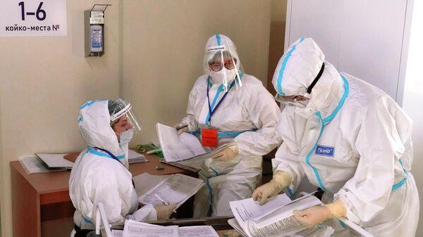Медицинские работники на медицинском посту во временном госпитале для больных COVID-19, организованном в выставочном комплексе Ленэкспо