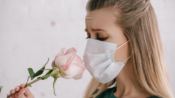 Девушка нюхает розу в медицинской маске