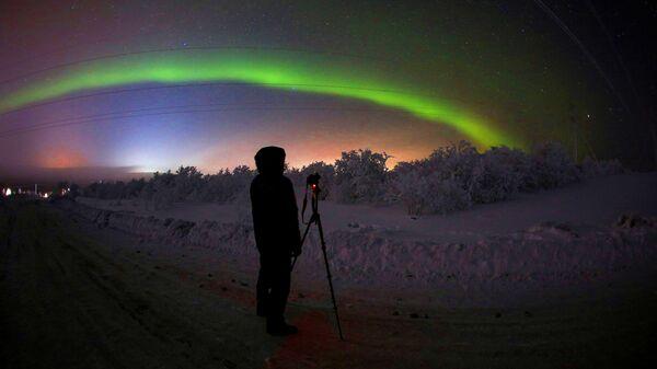 Мужчина фотографирует северное сияние на трассе Серебрянка в Мурманской области