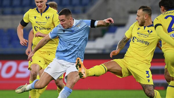 Lazio's Serbian defender Adam Marusic (L) shots over Verona's Italian defender Federico Dimarco during the Italian Serie A football match between Lazio and Verona at the Olympic stadium in Rome, on December 12, 2020. (Photo by Vincenzo PINTO / AFP)