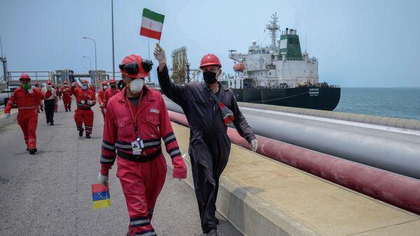 Сотрудники нефтяных компаний с флагами Венесуэлы и Ирана в порту Венесуэлы